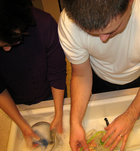 A man and woman wash dishes together at a sink full of soapy water.