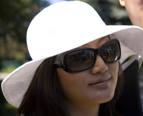 A woman wears a white sun hat with a large brim all the way around that shades her face and hair.