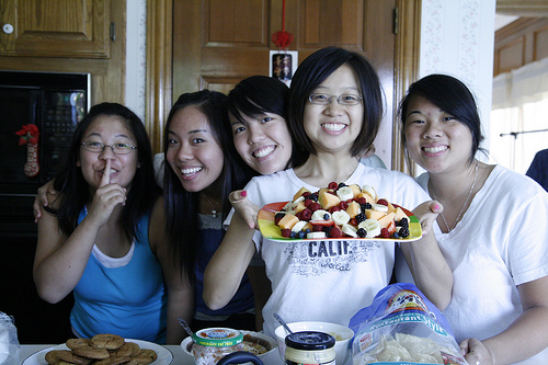 Young women posing in a kitchen. One holds a plate of fruit. Another puts her finger to her lips.