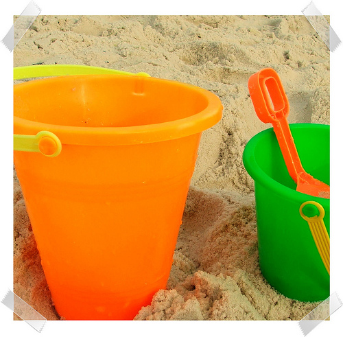 Two plastic beach pails, one orange and one green, with an orange plastic shovel.