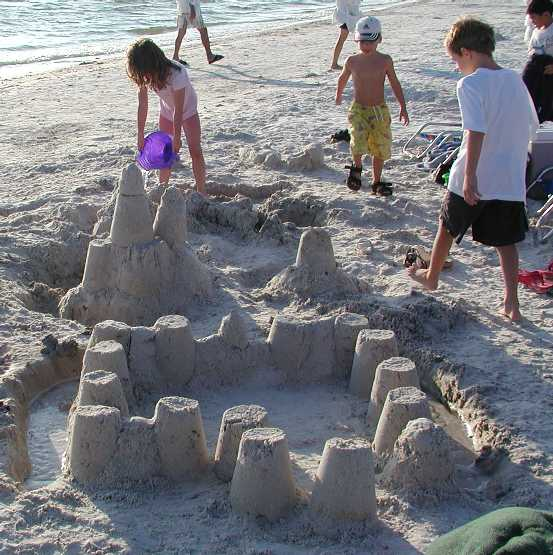 children building sand castles at a beach
