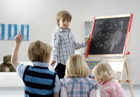 Child at blackboard teaching other children
